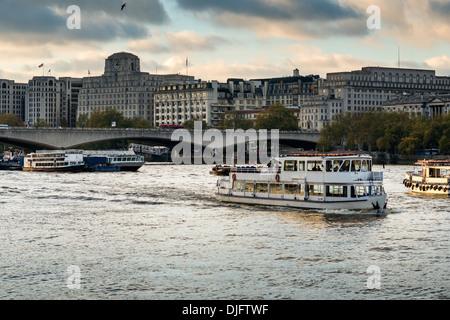 Thames pleasure cruises pass under Waterloo Bridge; landmark building Shell -Mex House forms the backdrop - Stock Photo