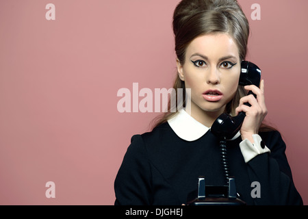A beautiful young woman holding a vintage phone receiver to her ears, stunned, surprised. She is dressed in a 60s - Stock Photo