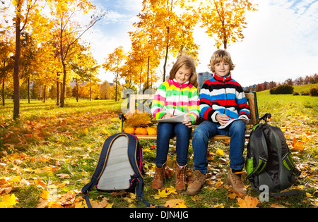 Portrait of two happy blond kids, twins brother and sister sitting on the bench after school  - Stock Photo