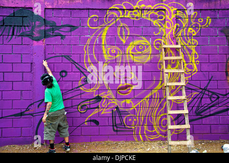 One of the graffiti artists working on his graffiti, still only working on the lines. - Stock Photo