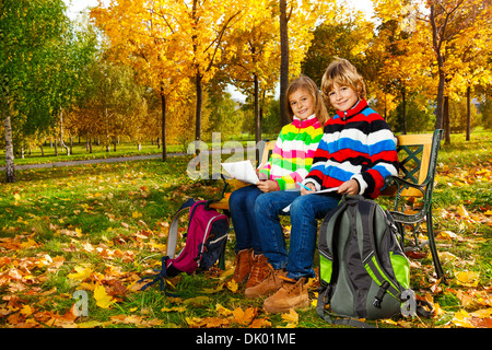 Portrait of two happy blond kids, twins sitting on the bench after school drawing pictures on paper - Stock Photo