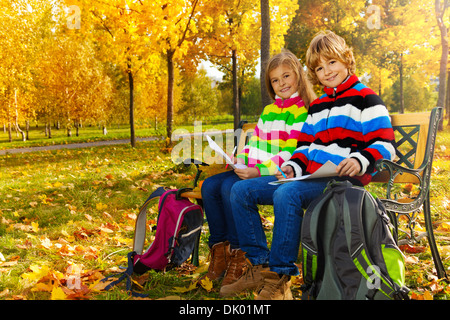 Portrait of two happy blond kids, twins sitting on the bench after school drawing pictures on paper with backpacks - Stock Photo