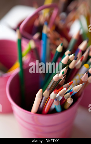 Close up high angle view of multicolor art colored pencils in pink bucket - Stock Photo
