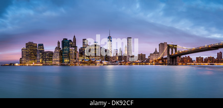 Lower Manhattan and the Brooklyn Bridge under a cloudy sky at dawn as viewed from the Brooklyn Bridge Park. - Stock Photo