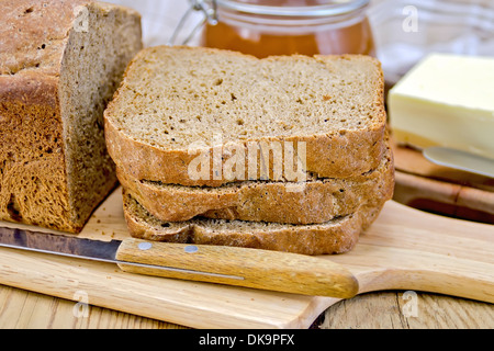 A stack of slices of rye homemade bread with a knife on a plate, napkin, loaf of bread, a jar of honey, butter on - Stock Photo