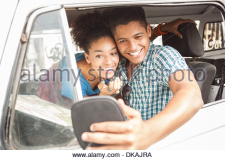 Young couple sitting in campervan, looking in wing mirror - Stock Photo