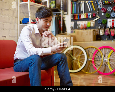 Young man sitting in bike shop using cell phone - Stock Photo