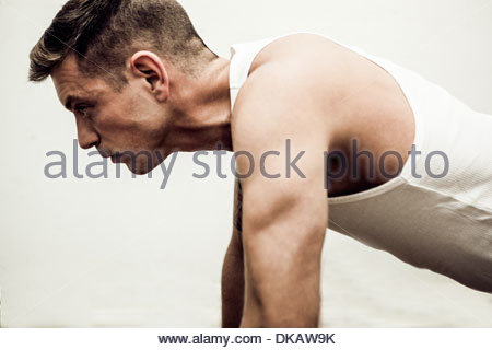 Close up of mid adult man doing push ups - Stock Photo