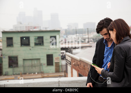 Couple listening to music on city rooftop - Stock Photo