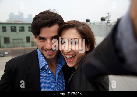 Couple taking self portrait on city rooftop - Stock Photo