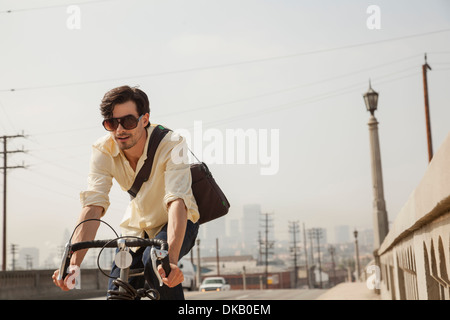 Man cycling on road, Los Angeles, California, USA - Stock Photo