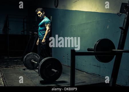 Weightlifter in dark gym, preparing to lift - Stock Photo