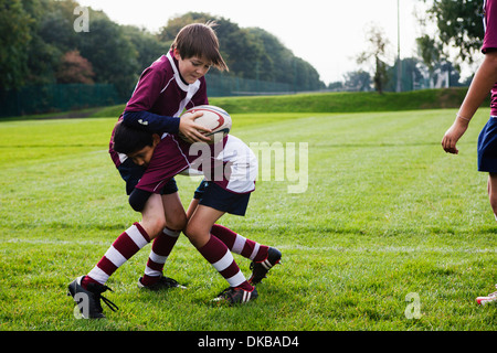Teenage schoolboy rugby team practicing defence - Stock Photo