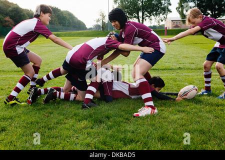 Teenage schoolboy rugby team practicing - Stock Photo