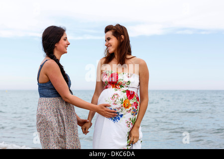 Woman with hand on pregnant friend's stomach - Stockfoto