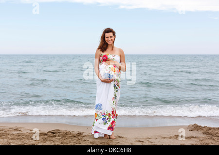 Pregnant woman standing on beach, hands on stomach - Stockfoto