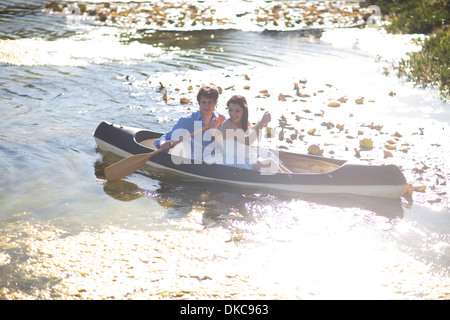 Young couple in rowing boat on river - Stockfoto