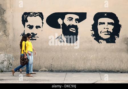 Cuban women walking past graffiti of heroes of the revolution including Che Guevara and Fidel Castro; Havana, Cuba, - Stock Photo