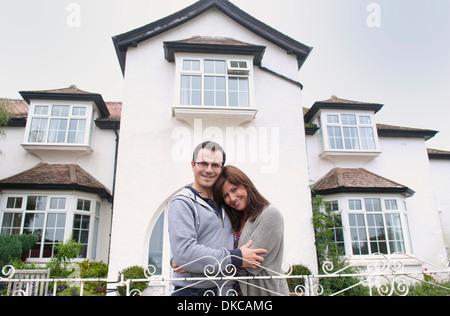 Portrait of couple outside house - Stock Photo