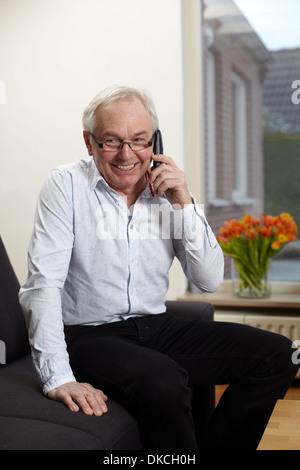 Senior man at home talking on mobile phone - Stock Photo