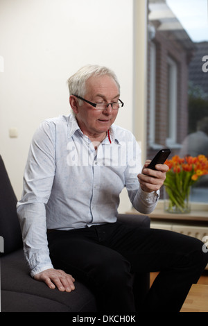 Senior man at home texting on mobile phone - Stock Photo