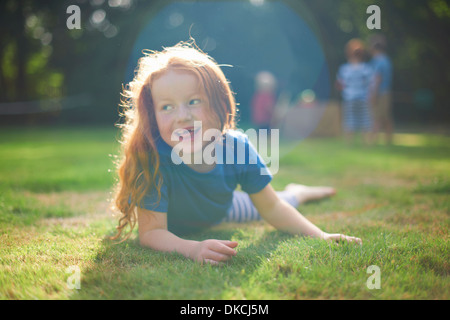 Happy young girl lying on grass in garden - Stock Photo