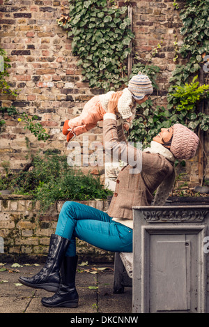 Mother throwing baby in air - Stock Photo
