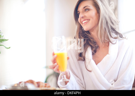 Young woman enjoying breakfast in bed - Stock Photo