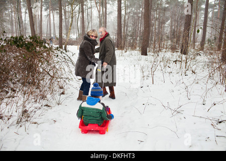 Grandparents pulling grandson on toboggan in snow - Stock Photo
