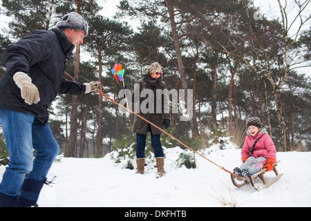 Father and grandmother pulling girl on toboggan in snow - Stock Photo