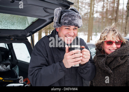 Mother and son having hot drink outside in winter - Stock Photo