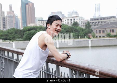 Male jogger taking a break on bridge - Stock Photo