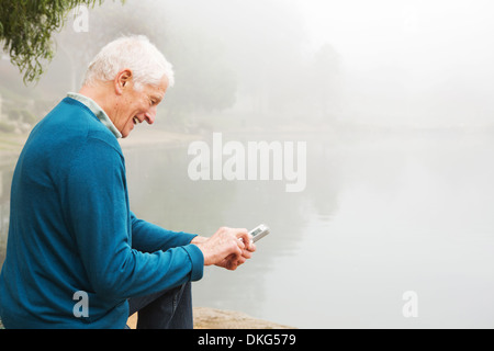 Senior man smiling at text on mobile phone - Stock Photo