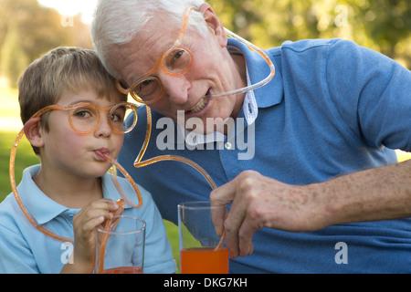 Grandfather and grandson drinking through straw eyeglasses - Stock Photo