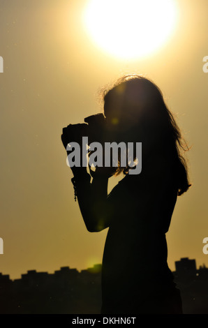 silhouette of girl isolated on sunset background in shooting time - Stock Photo