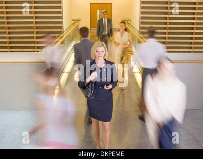 Businesswoman walking in busy office corridor - Stock Photo