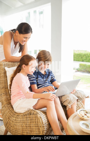 Mother and children using laptop in living room - Stock Photo