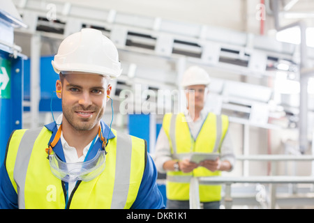 Workers smiling in factory - Stock Photo