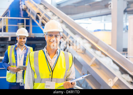 Workers smiling in recycling center - Stock Photo