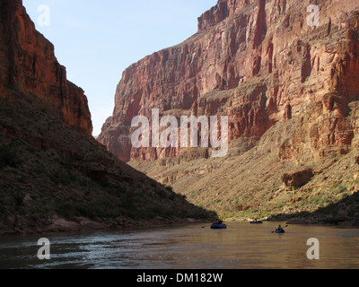 A group of boats work down the Colorado River through the Grand Canyon - Stock Photo