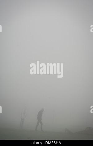 Walking figure in a London park on an early misty morning. - Stock Photo