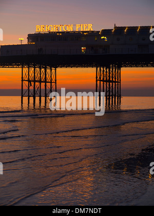 Brighton Pier sunset at low tide - Stock Photo