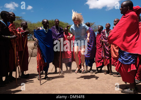 A young tourist dancing with Maasai warriors in the Ngorongoro Conservation Area in  Crater Highlands of Tanzania - Stock Photo