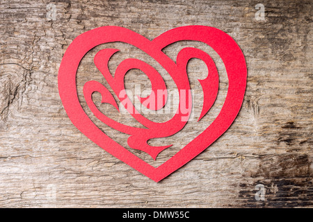Red Paper Cut out Heart with ornament on grunge wood background - Stock Photo