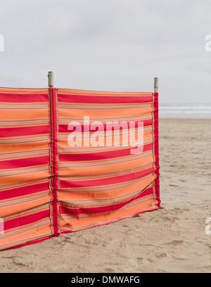 A red striped windbreak on Cannon Beach on  Oregon coast. - Stock Photo