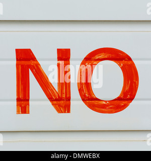 A large NO sign in red paint on a garage door indicating No Parking. - Stock Photo