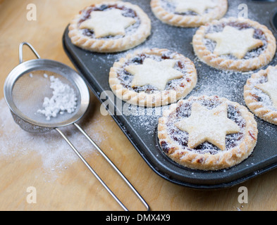 Home made icing sugar dusted mince pies in baking tray with sieve on wooden surface - Stock Photo