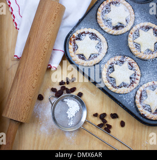Home made icing sugar dusted mince pies in baking tray - Stock Photo