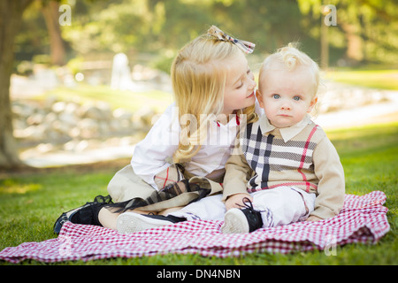 Sweet Little Girl Kisses Her Baby Brother on His Cheek Outdoors at the Park. - Stock Photo
