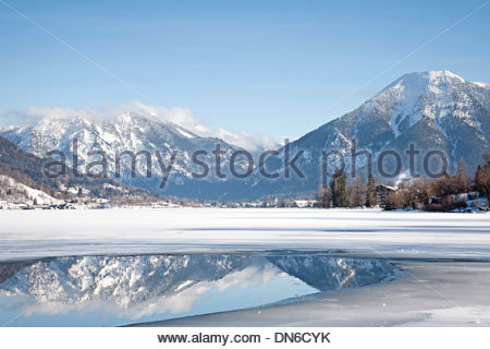 Ice hole on the Tegernsee with mirror image of the Wall Mount - Stock Photo